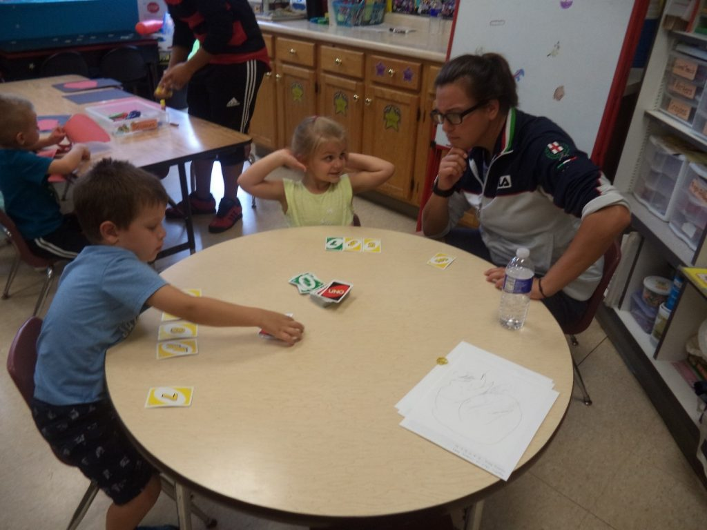 pre-schooler playing card game with adult